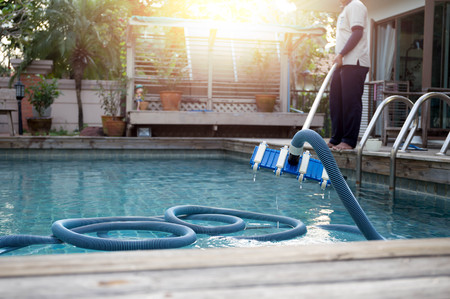 Man cleaning swimming pool with vacuum tube cleaner early in the morning