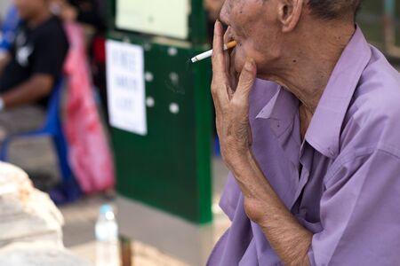 ciggy: Unhealthy old man smoking a cigarette outdoor