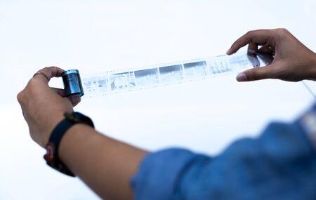 darkroom: Hands holding negative roll of film on white background