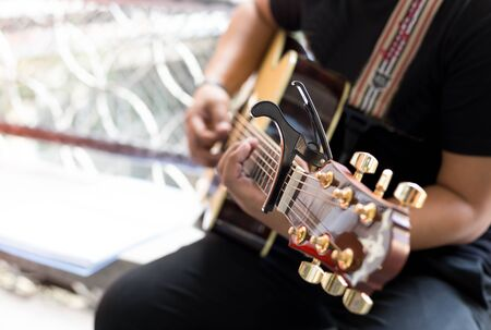 Man Practicing in playing acoustic guitar with a capo clip on guitar neck Stock Photo