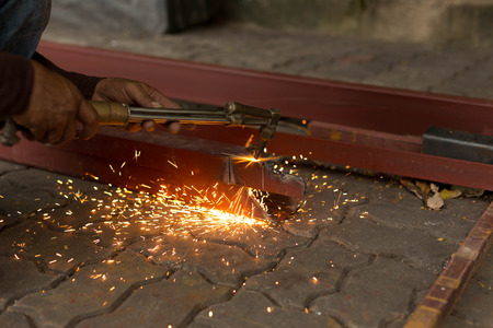 Man using torch cut metal plate in workshop Stock Photo