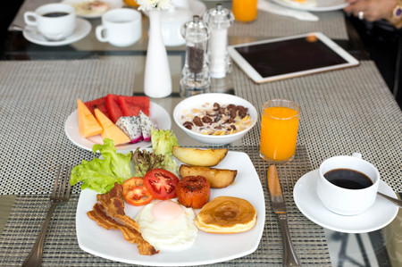 Breakfast set on the tabla with pancakes, bacon, eggs and coffee with Stock Photo