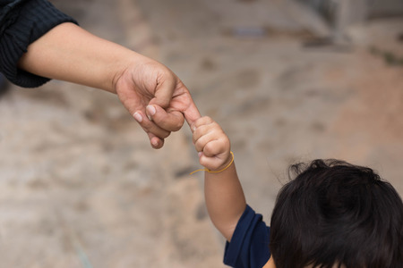 Little child holding her mothers finger while walking outside