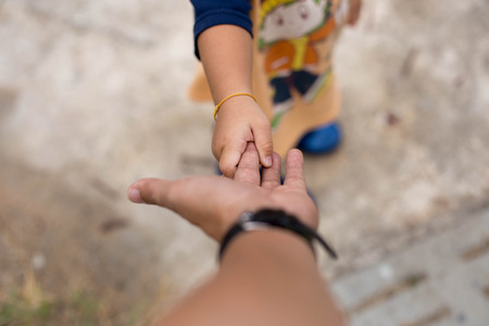 family unit: Little child holding her father is hand while walking Stock Photo