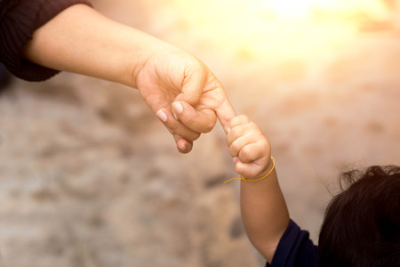 family unit: Little child holding her mothers finger while walking in sunlight flare