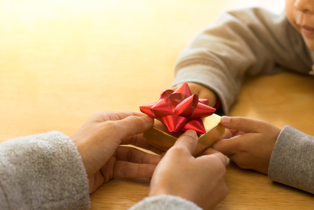 Young child handing a gift box to mum on special day