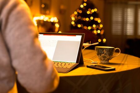 Businesswoman typing on laptop working at home on Christmas time with cup of coffee