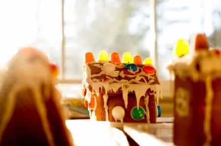 Soft focus Gingerbread House on the table next to window with sunlight