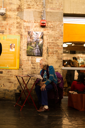 chelsea market: Dec 29, 2016 : Senior woman sitting in a chair reading news paper at Chelsea Market in New York City Stock Photo