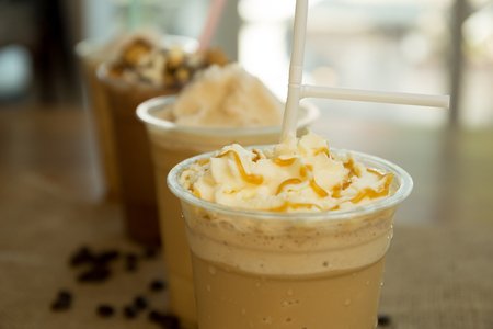Iced caramel coffee frappe with whipped cream in plastic glass in blur background Standard-Bild
