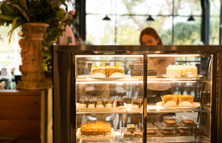 Woman buying some pastries in a cake shop on a refrigerator