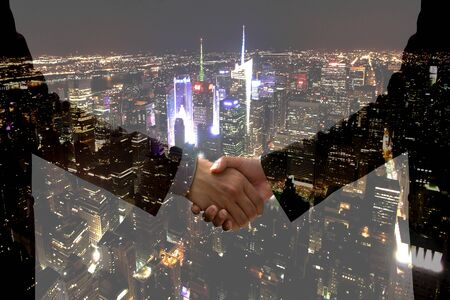 Double exposure Business hand shake with city light at night time Stock Photo