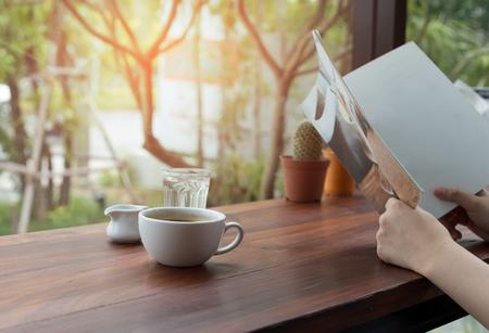 Los asiáticos que leen el libro y la taza de café fresca en la tabla