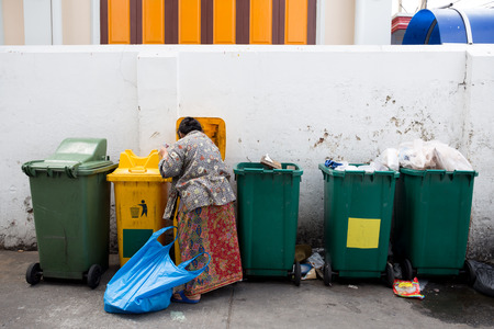 homeless woman is searching the trash in a trash bin on street Stock Photo