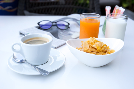 Breakfast set with cornflakes and cup of coffee and orange juice on white table