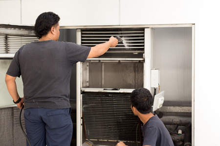 Unidentified man cleaning conditioner filter with high pressure water jet pump
