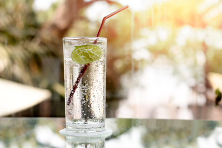 Glass of fresh sparkling mineral water and a lime in blur blackground