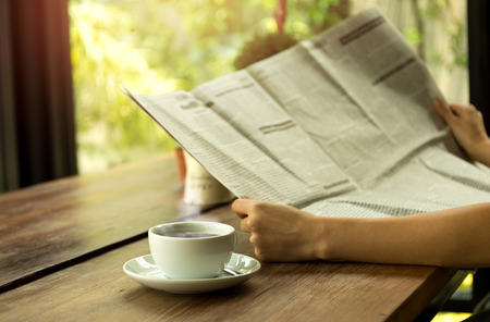 Business people having coffee and reading newspaper on wooden table Stock Photo