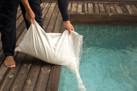 Man putting salt chlorinator for treatment water in swimming pool in the morning
