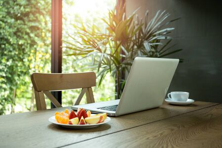 Wooden desk with fresh fruits and laptop with green plant in background