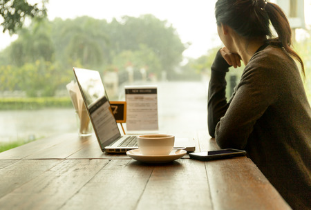 Asian woman with laptop with coffee on the table watching the rain out of window