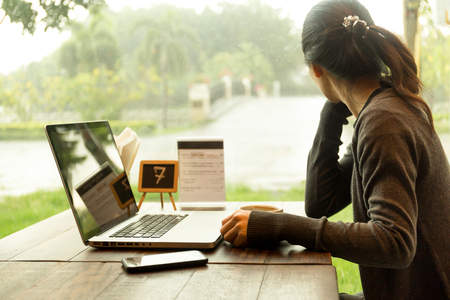 Young casual woman with laptop and having coffee watching the rain out of window