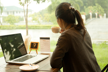 Asian woman with laptop having coffee watching the rain out of window Foto de archivo