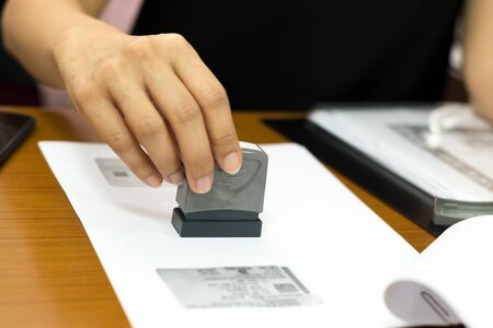 Business woman hand stamping approved document contract in office