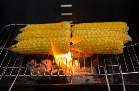 Fresh corn on the cob barbecue sizzling on charcoal with flame Stock Photo