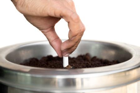 Vorgewählte Fokuszigarettenstummelhand, die heraus eine Zigarette im Aschenbecher lokalisiert auf weißem Hintergrund stummt Standard-Bild
