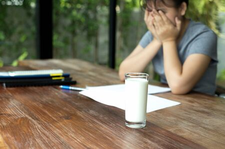 baffle: Asian teenager hand cover her face frustrated to do homework with glass of milk on the table Stock Photo