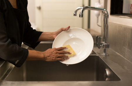 sink: Woman washing the dishes in kitchen sink in the restaurant Stock Photo