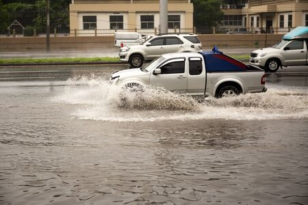Car driving through flood water on the road during monsoon season Stock Photo