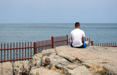 Man sitting on the rock doing meditation by the sea in day time