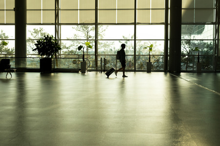 Silhouette traveler man  walking in airport terminal gate for airplane travel