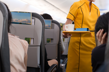 Flight attendant offering beverage to a passenger in flight jurney 免版税图像
