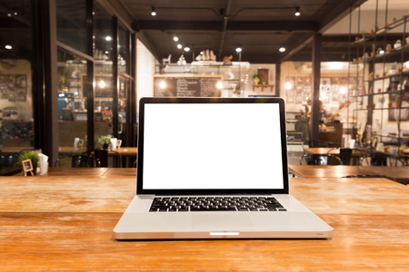 front desk: Laptop with blank screen on wooden table in coffee shop