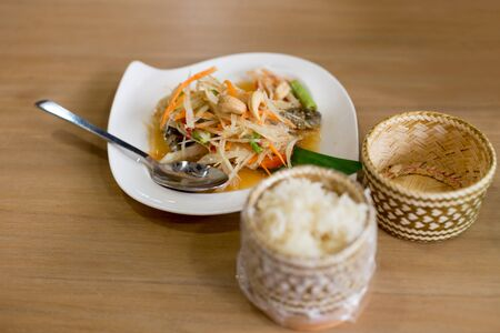 Som Tum papays salad on wooden table with sticky rice Stock Photo