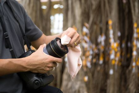 Photographer cleaning a camera lens with a micro cloth at workplace