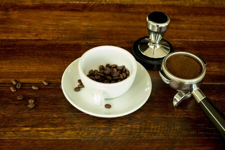 black metallic background: Concept and idea cup with coffee beans and and coffee ground on wooden table