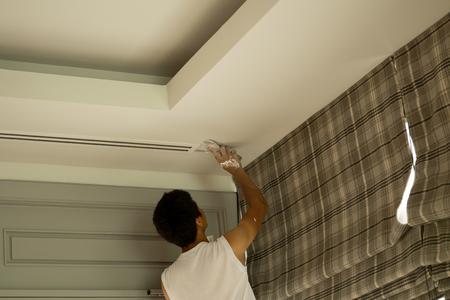 Builder repair using gypsum plaster ceiling at construction site