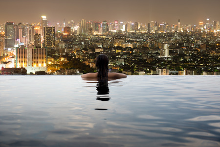 Young woman in outdoor swimming pool with city view at night Stockfoto
