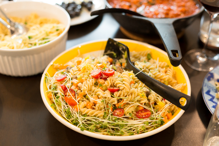 olive green: Pasta salad with cherry tomato with sunflower sprouts and parmesan cheese in yellow blow Stock Photo