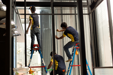 Unidentified worker applying tinted layer on glass window in summer