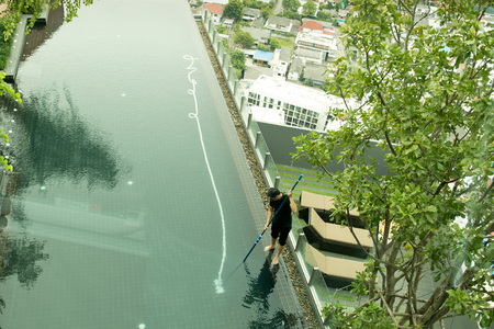 Top view man cleaning resort swimming pool with vacuum tube cleaner