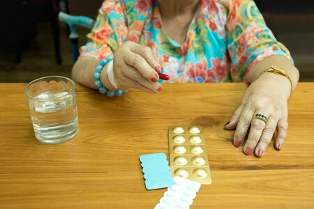 Health care concept fat senior woman hand holding pills and glass water on wooden table
