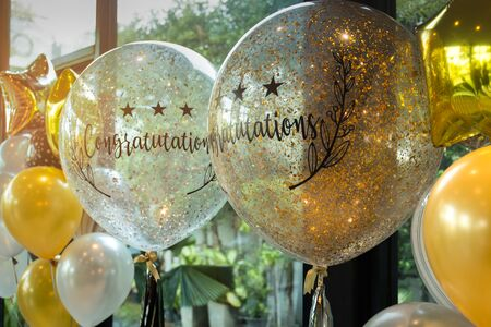 reflection: Celebration Gold and white balloons with sparkles and Congratulation text at party decorations Stock Photo