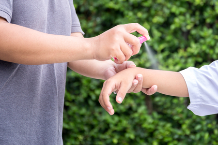 Mother spraying insect repellents on her son arm in the garden Stock Photo