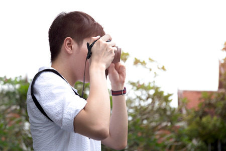 Young man tourist taking photos of landscape compact camera on vacation