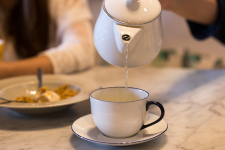 Hand pouring tea from teapot into tea cup on the table Stock Photo